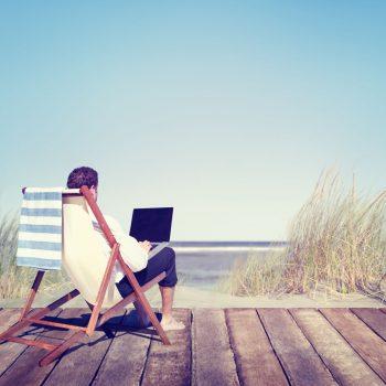 Man on beach chair on laptop
